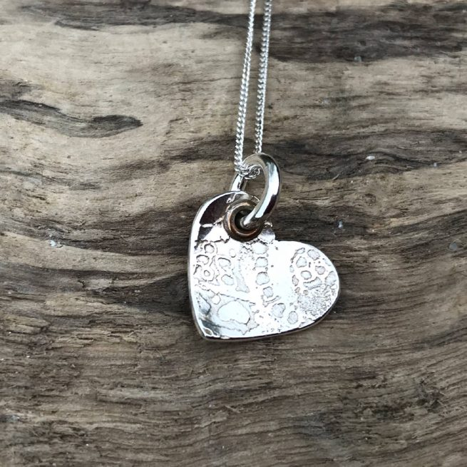 sterling silver textured heart necklace rests on wood