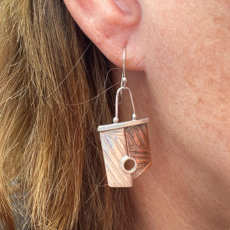 handcrafted sterling silver and copper two toned mismatched earrings modelled