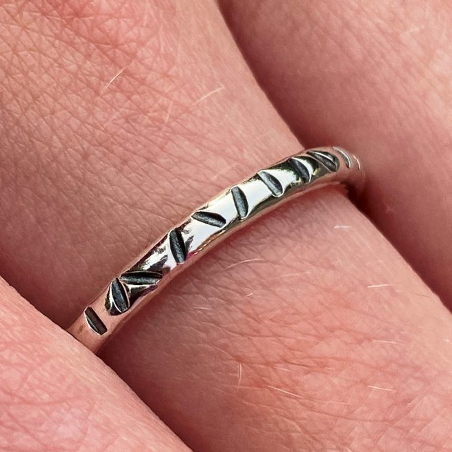 sterling silver stacking ring with a linear textured design modelled