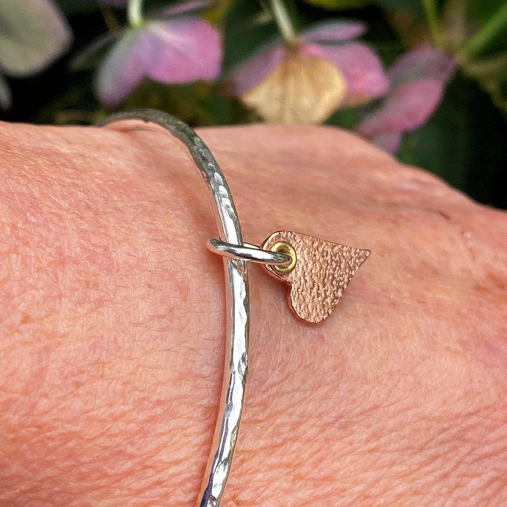 sterling silver minute heart bracelet is show on a woman's wrist