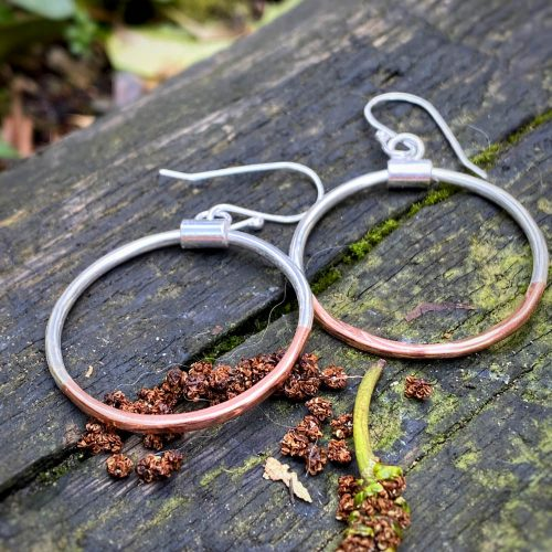 sterling silver and copper hoop earrings lay on a piece of wet wood