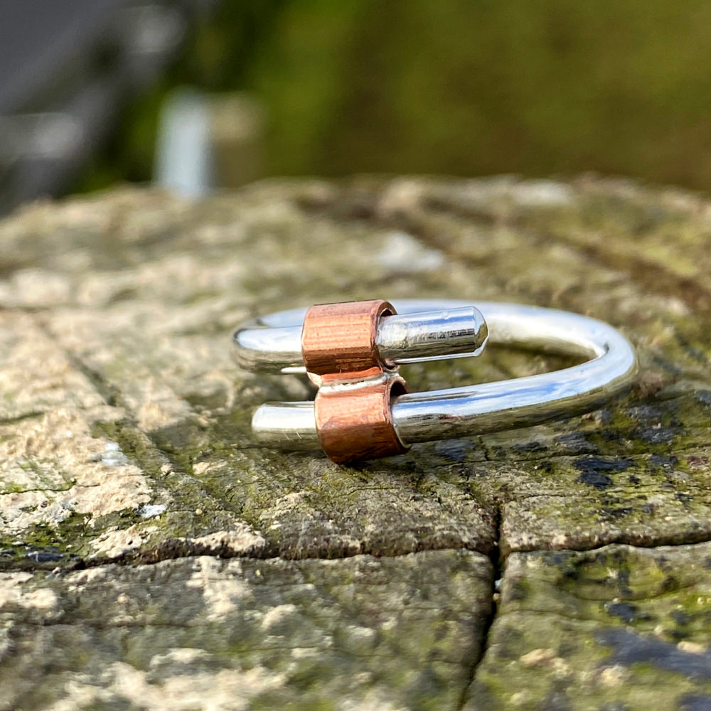 close up image of the sterling silver and copper tube handmade ring on a piece of wood