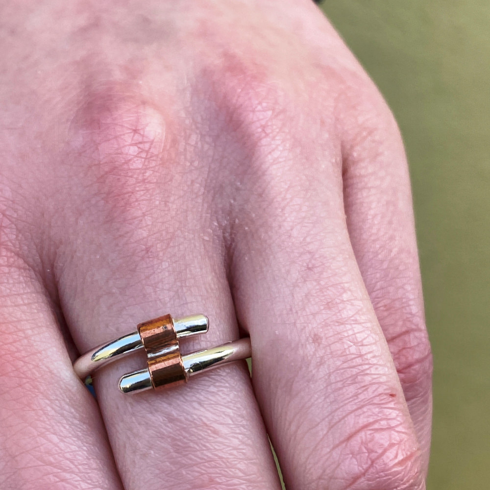 model is wearing the sterling silver and copper tube ring on her middle finger