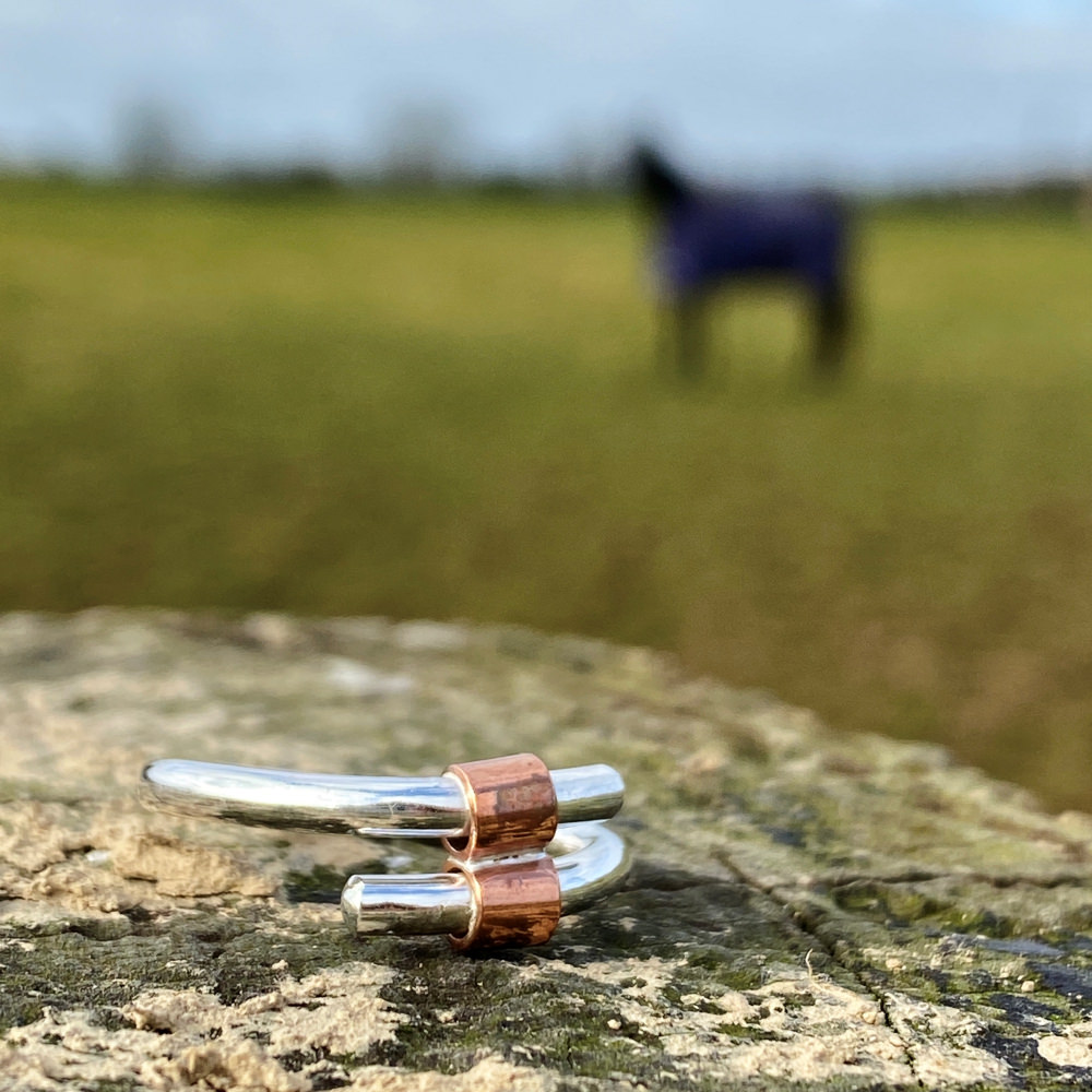 the sterling silver and copper tube ring placed on a rock with a blurred image of a horse in the backbround