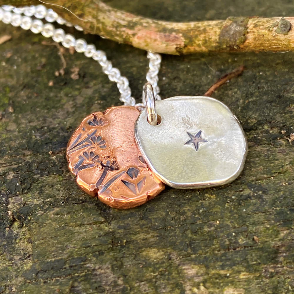 closeup of the necklace . the sterling silver piece has a hand stamped star and the copper disc has floral images stamped