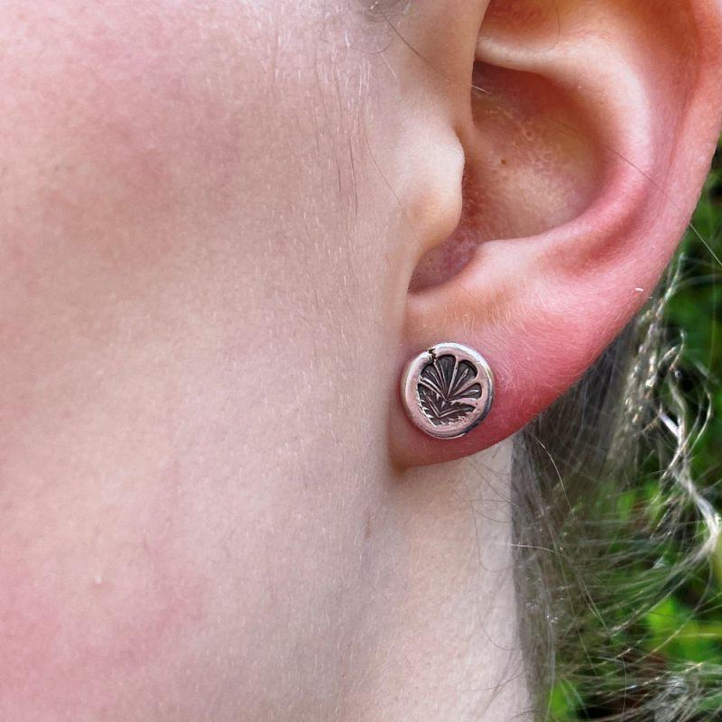 model is wearing the sterling silver leafy stud earring in her ear