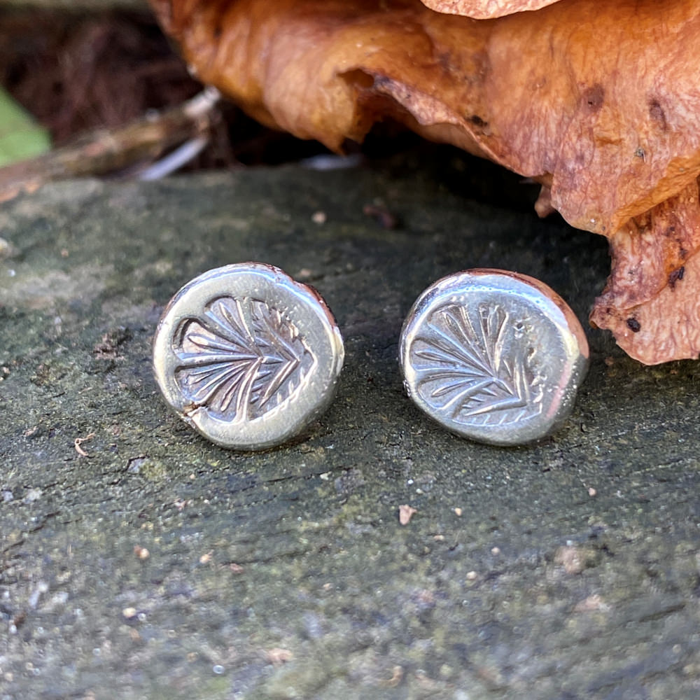 hand forged sterling silver earrings stamped with a tropical leaf rest on a rock with a brown lead in background
