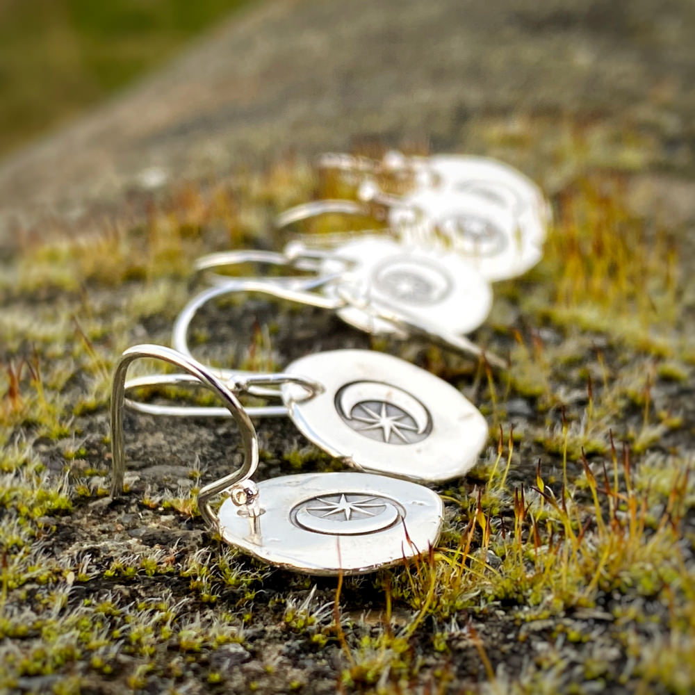 3 pairs of moon and start sterling silver earrings lay on a piece of moss