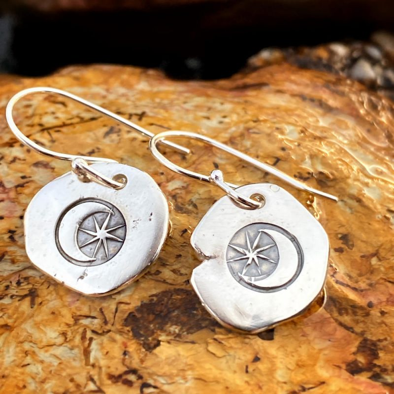 sterling silver discs hand stamped with a moon and stars with handmade earwires lay on a rock