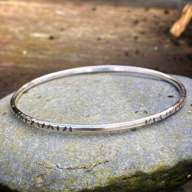 "stacking bangle bracelet design ""linear"" lies on a rock"