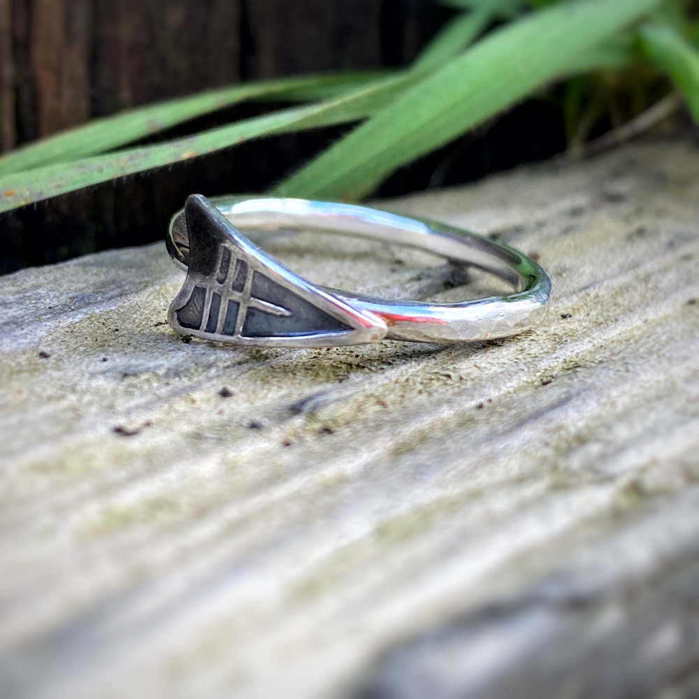 sterling silver arrow ring with a patina finish lies on a piece of driftwood