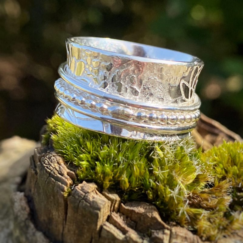 sterling silver spinner ring with 3 spinners lies on a piece of wood with moss