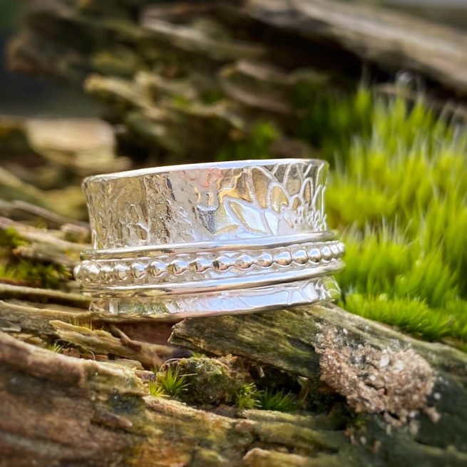 sterling silver ring with three spinners lies on a piece of drift wood
