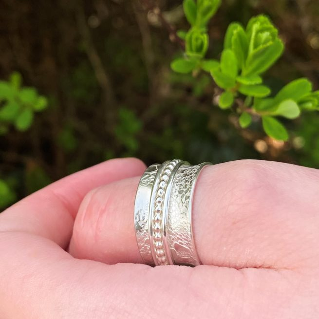 model is wearing the sterling silver spinner ring with 3 spinners on her thumb