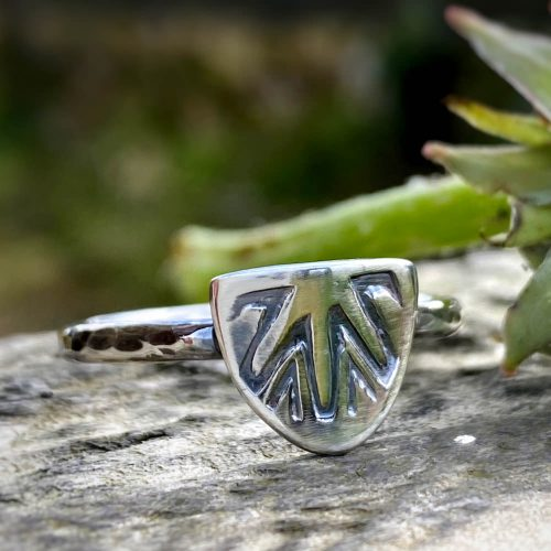 sterling silver ring with a shield motif lies on a piece of driftwood
