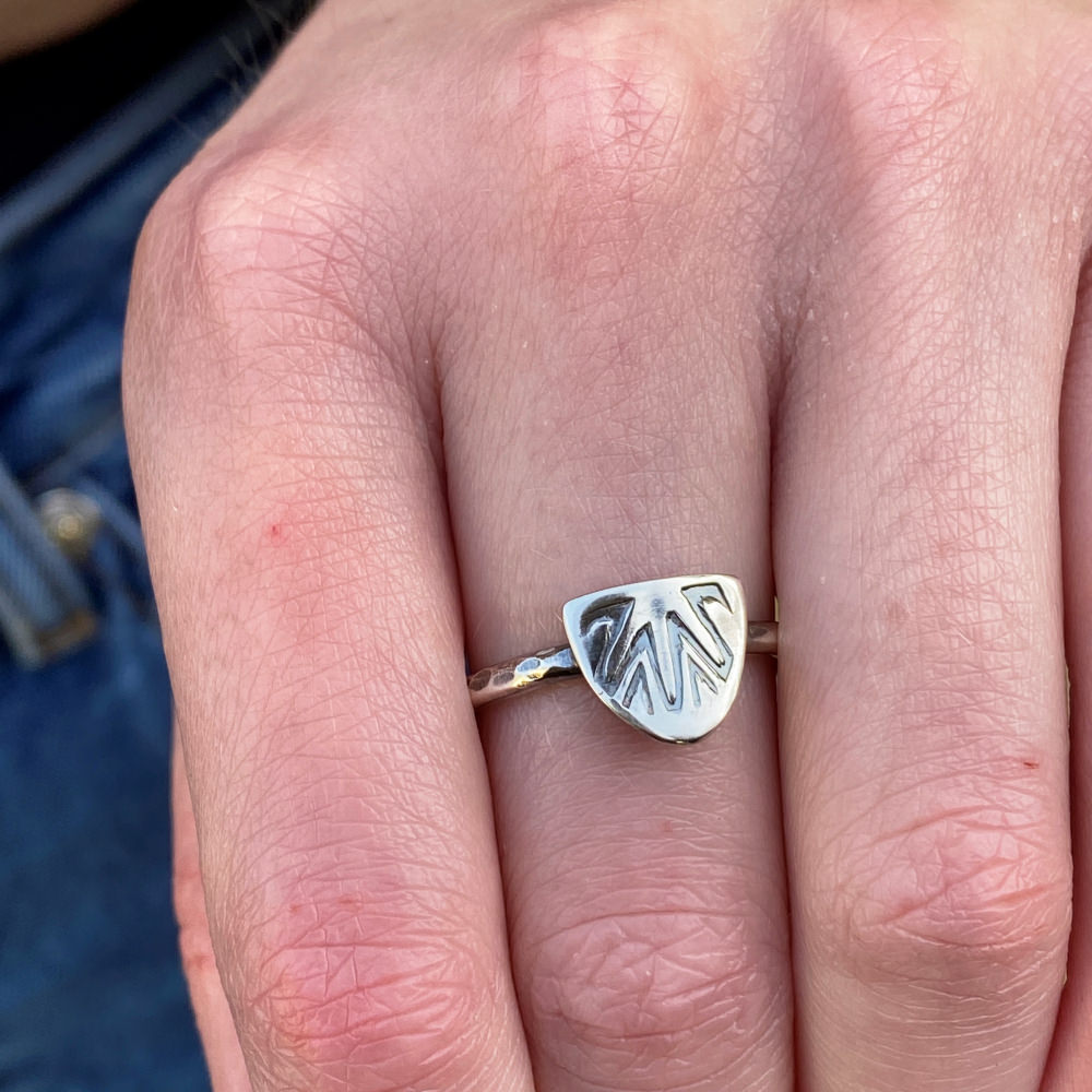 model is wearing the sterling silver shield ring on her middle finger
