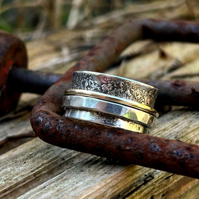 wide band of sterling silver and a thin bank of 9kt gold spin on the band of sterling silver